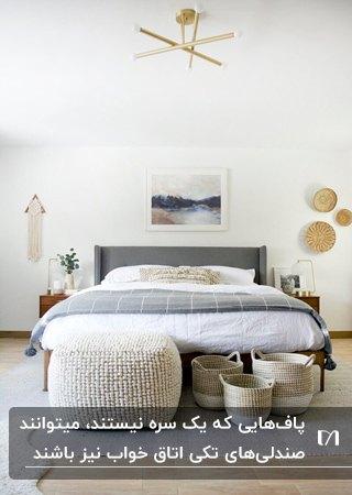 اتاق خواب مدرنی با تخت طوسی، پاف بافتنی مکعب و سه سبد حصیری در سایزهای مختلف