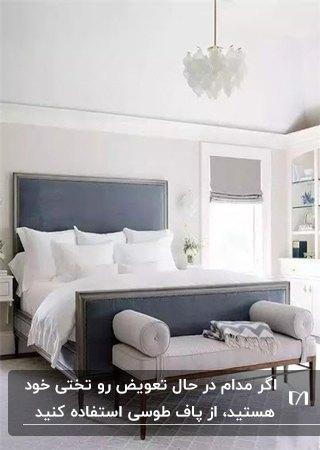 یک تخت کلاسیک خاکستری با روتختی و کوسن های سفید به همراه پاف دسته دار طوسی