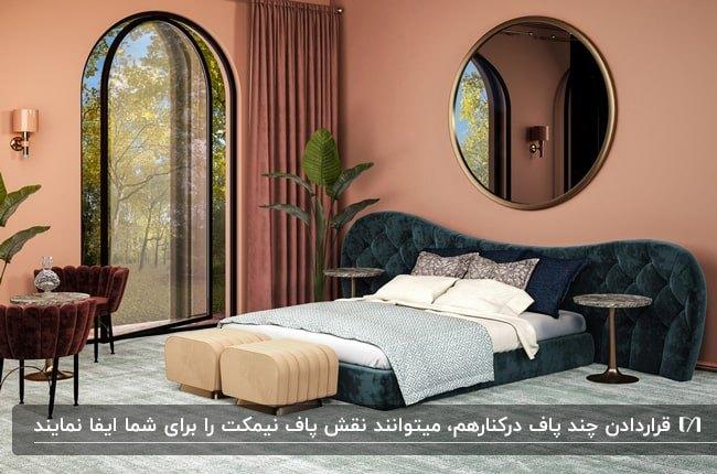 اتاق خوابی با دیوارهای صورتی، تخت مخمل سبز تیره، پاف های کرم و آینه گرد بزرگ بالای تخت