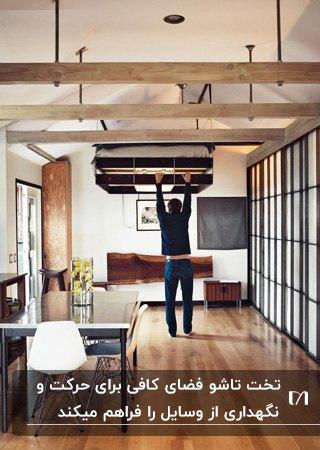 تخت تاشوی آسانسوری در خانه ای با کف پارکت و سقف به همراه تیرهای چوبی
