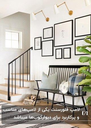نیمکت چوبی کنار راه پله و قاب هایی در سایزهای مختلف بالای آن به همراه دیوارکوب سفید و طلایی