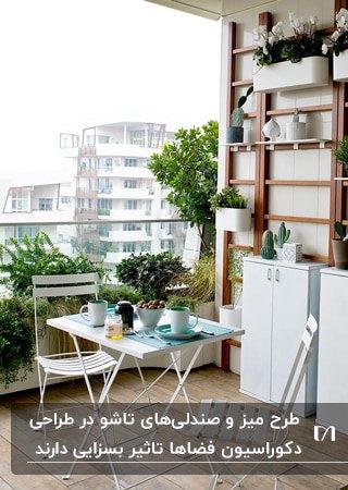 میز و صندلی کوچک دو نفره فلزی به رنگ سفید روی تراسی با نرده شیشه ای