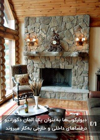 نشیمنی روستیک با دیوار سنگی شومینه، صندلی تک نفره و دو چراغ دیواری بالای طاقچه شومینه