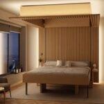 اتاق خوابی نورپردازی شده با تخت آسانسوری چوبی هماهنگ با دیوارپوش چوبی اتاق