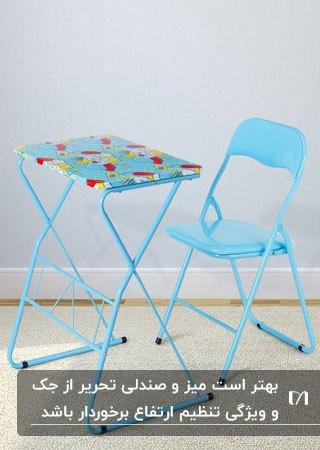 تصویر یک میز و صندلی تحریر تاشو فلزی به رنگ آبی با طرح های زرد و قرمز