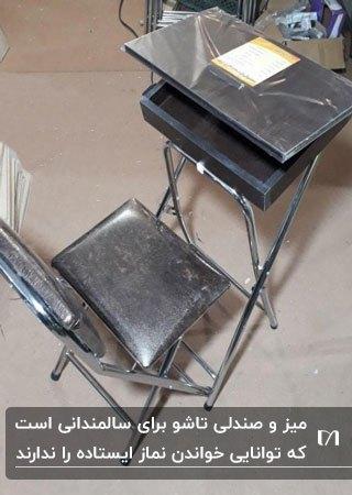 تصویر یک صندلی تاشو تیره برای نماز به همراه باکس