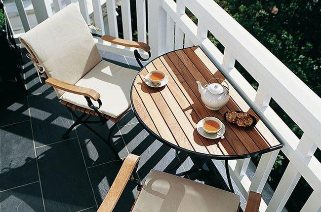 تصویری از یک میز نیم دایره دیواری و دو صندلی چوبی با پایه های فلزی کنار نرده بالکن