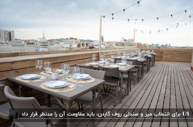 تصویر رستورانی در روف گاردن با میز و صندلی های طوسی تاشو با کفپوش چوبی