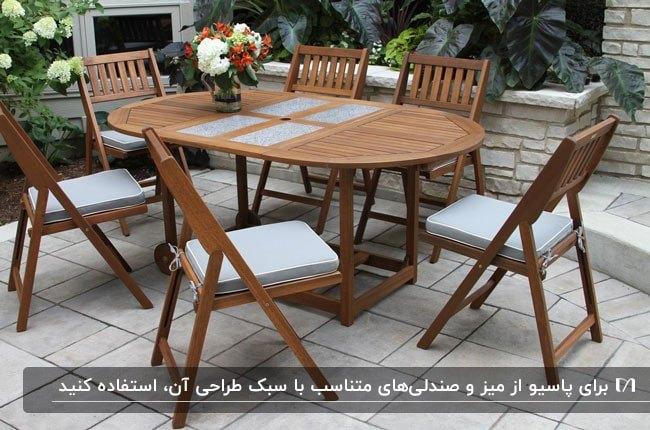 تصویر یک میز چوبی بیضی شکل به همراه شش صندلی تاشو از جنس چوب در پاسیو