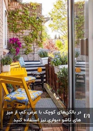 یک بالکن کوچک با میز و دو صندلی تاشوی زرد و نشیمنگاه آبی با گلهای زرد