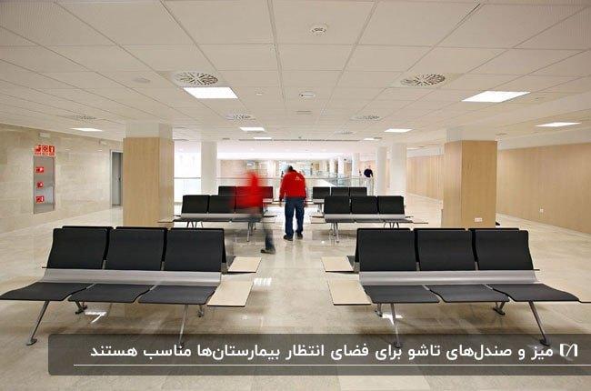 تصویری از سالن انتظار یک بیمارستان با صندلی های تاشوی مشکی