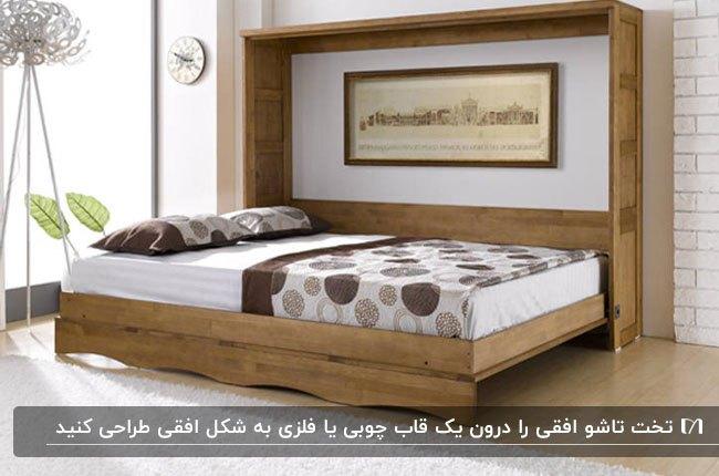 تصویر یک تخت تاشو دیواری با رو تختی کرم و قهوه ای که بصورت افقی جمع میشود