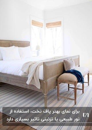 تصویر اتاق خوابی با تخت پایه دار چوبی و پافی با پایه چوبی و پارچه کرم رنگ