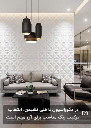 نشیمنی با مبل طوسی و قهوه ای، لوستر آویز و یک دیوارپوش طرح برجسته پشت مبلمان