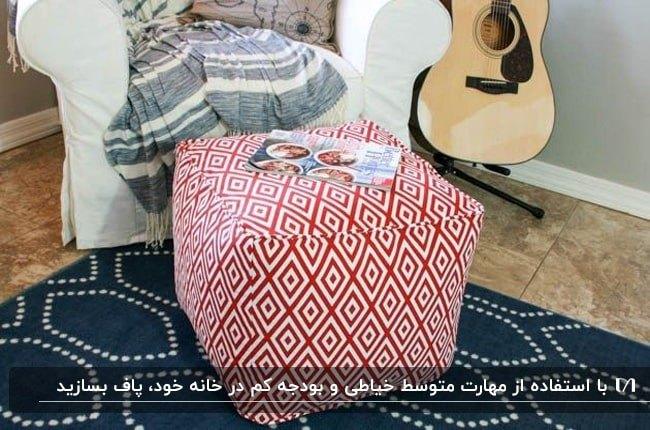 تصویر یک پاف مربعی با پارچه طرحدار قرمز و سفید کنار مبل و گیتار و فرش سرمه ای