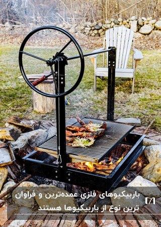 تصویر یک کباب پز فلزی به رنگ مشکی روی آتش در فضای باز