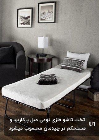 تخت تاشوی فلزی مشکی با تشک و بالشت سفید کنار یک کاناپه خاکستری و دیوار طوسی