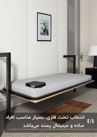 تصویر یک تخت تاشوی دیواری فلزی مشکی با تشک طوسی