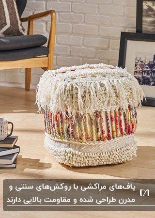 تصویر یک پاف مکعبی مراکشی با پارچه های رنگی کنار صندلی