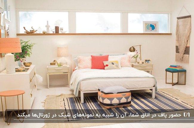 تخت خوابی کرم و سفید با کوسن های صورتی، فرش راه راه سرمه ای و کرم له همراه پاف طرحدار مربعی