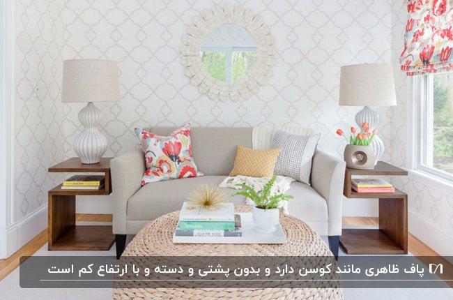 تصویر یک نشیمن با کاغذدیواری طرحدار، کاناپه دو نفره، دو آباژور و پاف حصیری