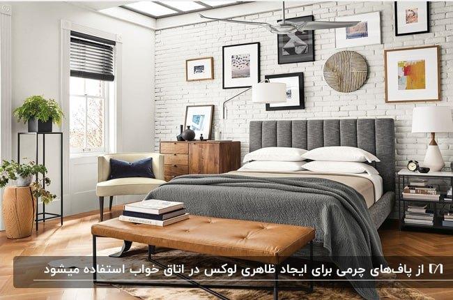 اتاق خوابی با تخت طوسی، قاب هایی روی دیوار، کنسول چوبی و پاف تخت چرم قهوه ای