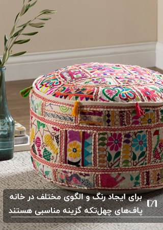 تصویر یک پاف دایره ای چهل تکه با رنگ های شاد کنار بطری شیشه ای با گل در آن