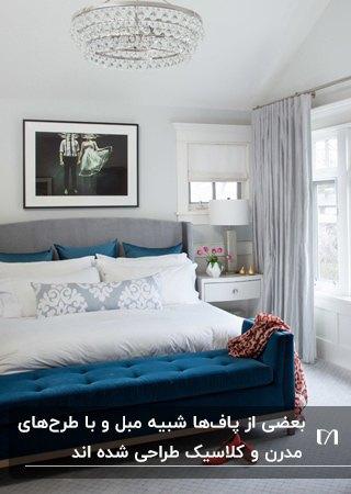 تصویر یک تخت طوسی با کوسن های مخمل آبی و پاف دسته دار از جنس مخمل آبی کوسن ها