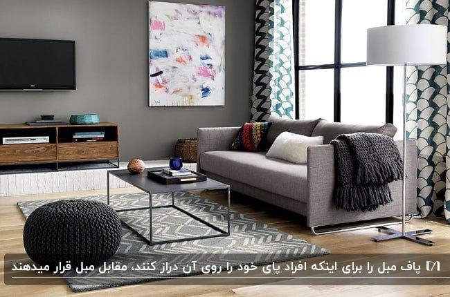 تصویر نشیمنی طوسی و خاکستری با کاناپه طوسی، میز فلزی مشکی، پاف خاکستری و تلویزیون روی دیوار