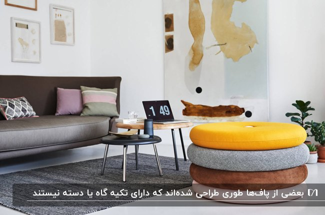 تصویر یک پاف استوانه بدون دسته رنگی مقابل کاناپه چوبی و میزهای عسلی گرد