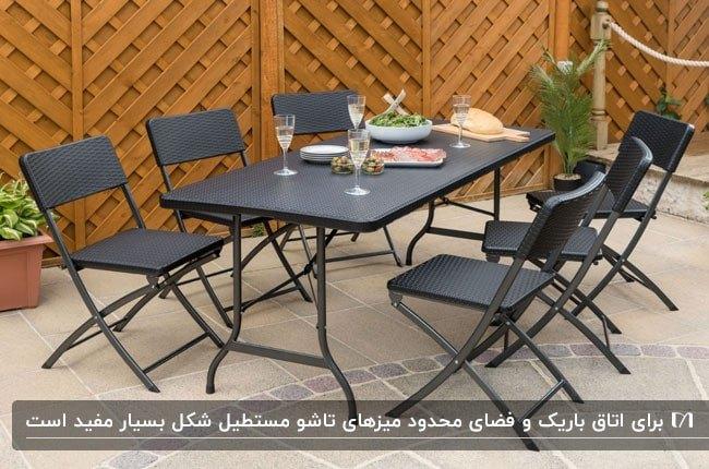 تصویری از میز و صندلی های شش نفره مستطیلی مشکی مقابل دیوار چوبی