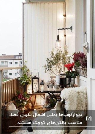 بالکن کوچک و زیبایی با میز چوبی،گلدان های گل، فانوس های شمع و چراغ دیواری