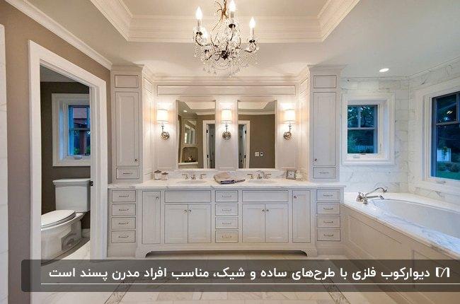 حمام و سرویس بهداشتی بزرگی با دو آینه بالای روشویی و سه چراغ دیواری بین آینه ها