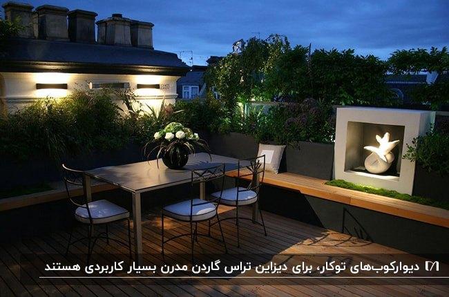 تصویر تراش گاردنی با میز و صندلی های مشکی و نیمکت چوبی به همراه چراغ های دیواری دکوراتیو