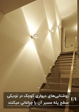 راه پله ای با پله ها و نرده استیل به همراه دیوارکوب هایی با تابش نور به بالا و پایین