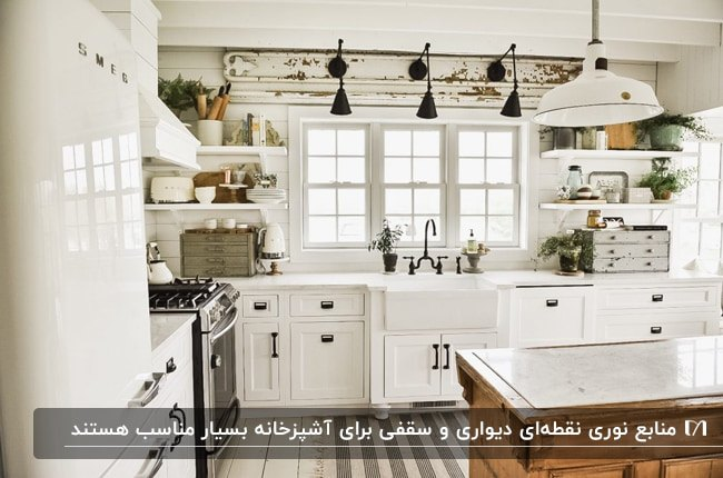 آشپزخانه ای با کابینت های سفید و جزیره به رنگ طبیعی چوب با دیوارکوب های مشکی بالای پنجره