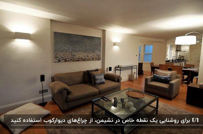 نشیمنی با مبلمان راحتی قهوه ای، تابلوی نقاشی روی دیوار و چراغ های دیواری دو طرف تابلو