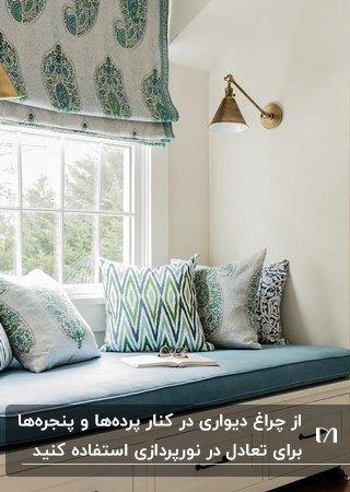کنج دنج کنار پنجره با پرده سفید و آبی، نیمکت با دشکچه آبی و دیوارکوب طلایی