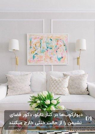 نشیمنی با مبلمان سفید و کوسن های طرحدار کمرنگ، تابلوی نقاشی روی دیوار و دو دیوارکوب سفید و طلایی