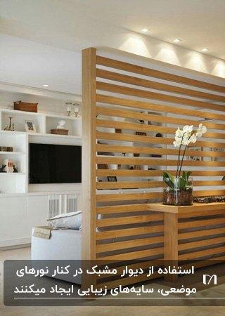 دیوار مشبک چوبی در نشیمن بجای پارتیشن با دیوارکوب هایی بالای آن برای روشنایی