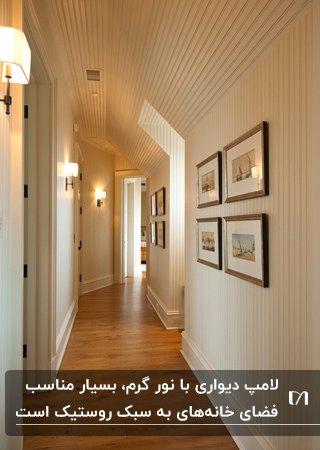 راهروی خانه ای با کاغذدیواری سفید و کرم راه راه به همراه دیوارکوب کنار درب اتاق ها