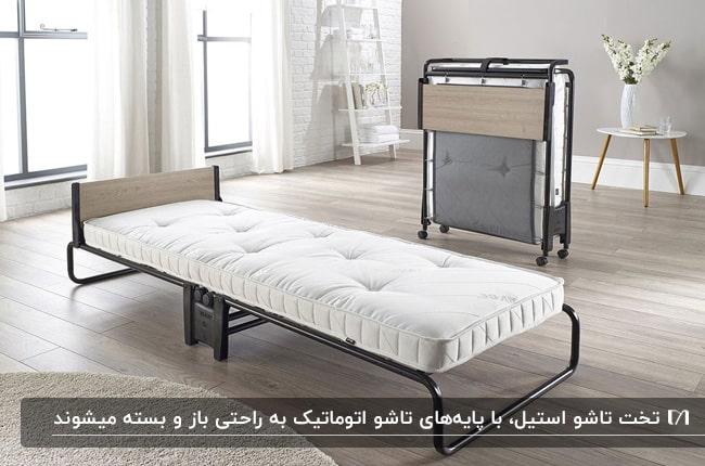 تصویر یک تخت تاشو از جنس استیل خاکستری با تشک سفید