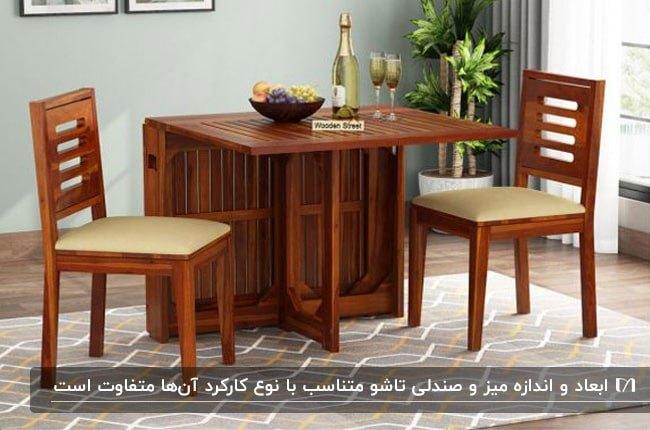 تصویر یک میز و دو صندلی تاشو از جنس چوب در خانه ای با دیوار طوسی