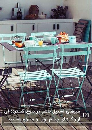 تصویر یک میز مربع و چهار صندلی استییل به رنگ آبی پاستلی در حیاط