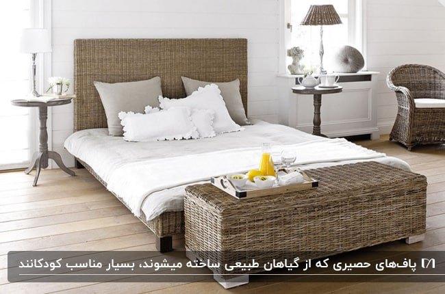 تخت خواب و پاف تخت حصیری قهوه ای با رو تختی و کوسن های سفید و طوسیو یک مبل تک نفره حصیری