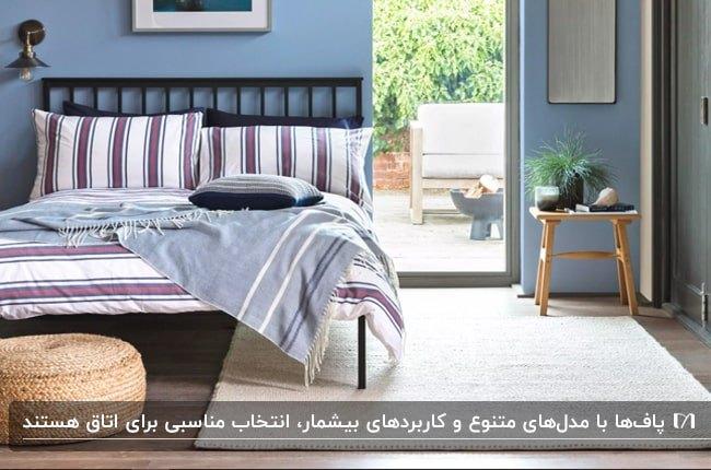 اتاق خوابی با دیوارهای آبی، تخت چوبی قهوه ای تیره با روتختی راه راه و یک پاف کوتاه حصیری گرد پایین تخت