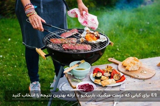 باربیکیو سیار و گودی کنار میز غذاخوری در حیاط