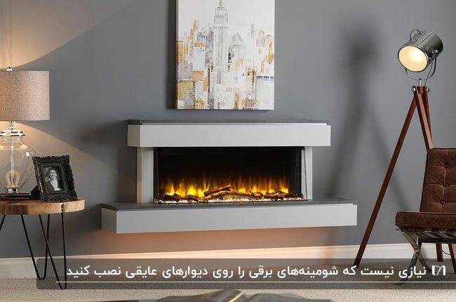 شومینه برقی طوسی روی دیوار خاکستری با آباژور و چراغ به همراه سه پایه