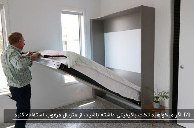 یک تخت تاشوی دیوار طوسی در اتاق با آقایی در حال جمع کردن تخت