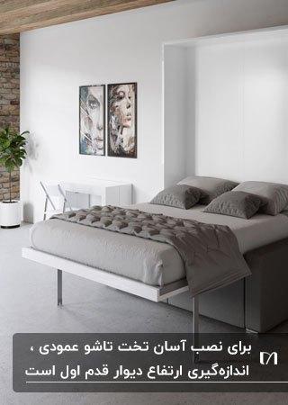 تصویر یک تخت تاشو دیواری با روتختی و بالشت طوسی که بصورت عمودی جمع میشود